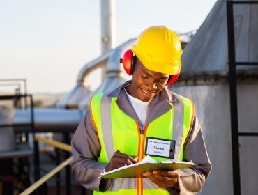 happy african american oil chemical industry worker working in plant